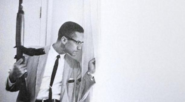 Malcolm X con una carabina in mano guarda fuori la finestra di casa. Da Life, 1964